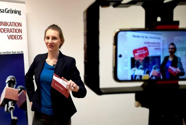 Gesa zeigt vor der Webcam wie digitales Moderieren geht